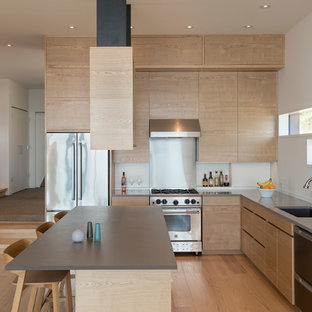This is an example of a mid-sized contemporary l-shaped open plan kitchen in Seattle with an undermount sink, flat-panel cabinets, light wood cabinets, quartz benchtops, grey splashback, slate splashback, stainless steel appliances, with island, brown floor and medium hardwood floors.