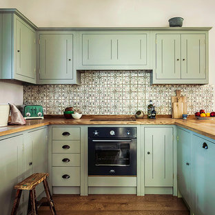 Inspiration for a country u-shaped kitchen in London with an undermount sink, beaded inset cabinets, green cabinets, wood benchtops, green splashback, mosaic tile splashback, black appliances and medium hardwood floors.