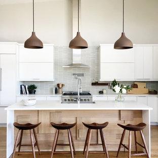 Offene, Große, Zweizeilige Moderne Küche mit Landhausspüle, flächenbündigen Schrankfronten, weißen Schränken, Quarzwerkstein-Arbeitsplatte, Küchengeräten aus Edelstahl, braunem Holzboden, Kücheninsel, braunem Boden, weißer Arbeitsplatte, Küchenrückwand in Grau, Rückwand aus Mosaikfliesen und gewölbter Decke in Denver