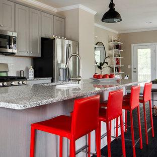 他の地域のエクレクティックスタイルのおしゃれなキッチン (アンダーカウンターシンク、落し込みパネル扉のキャビネット、グレーのキャビネット、御影石カウンター、白いキッチンパネル、セラミックタイルのキッチンパネル、シルバーの調理設備の、ラミネートの床、グレーのキッチンカウンター、黒い床) の写真