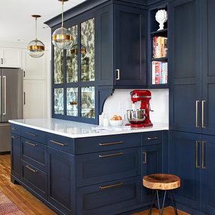 На фото: с высоким бюджетом угловые кухни среднего размера в стиле современная классика с обеденным столом, одинарной раковиной, синими фасадами, столешницей из кварцевого агломерата, белым фартуком, фартуком из плитки кабанчик, техникой из нержавеющей стали, паркетным полом среднего тона, полуостровом, коричневым полом, белой столешницей и фасадами в стиле шейкер