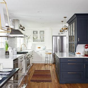 Inredning av ett klassiskt mellanstort vit vitt kök, med skåp i shakerstil, blå skåp, vitt stänkskydd, stänkskydd i tunnelbanekakel, mellanmörkt trägolv, brunt golv, bänkskiva i kvarts, rostfria vitvaror, en halv köksö och en enkel diskho