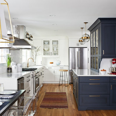 Eat-in kitchen - mid-sized transitional l-shaped medium tone wood floor and brown floor eat-in kitchen idea with shaker cabinets, blue cabinets, white backsplash, subway tile backsplash, quartz countertops, stainless steel appliances, a peninsula, white countertops and a single-bowl sink