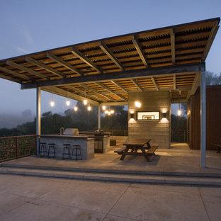 Modelo de cocina de galera, moderna, de tamaño medio, con encimera de cuarzo compacto, electrodomésticos de acero inoxidable y suelo de cemento