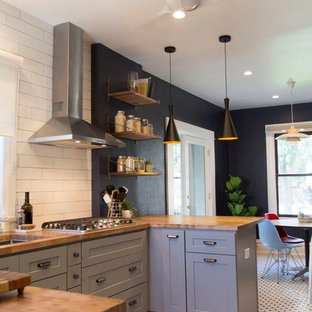 Photo of a mid-sized midcentury galley eat-in kitchen in Denver with an undermount sink, shaker cabinets, grey cabinets, wood benchtops, white splashback, ceramic splashback, stainless steel appliances, ceramic floors, a peninsula and white floor.