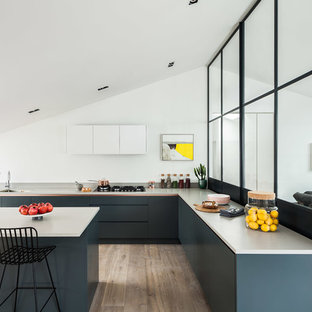This is an example of a medium sized contemporary l-shaped open plan kitchen in London with a double-bowl sink, flat-panel cabinets, blue cabinets, concrete worktops, an island and brown floors.