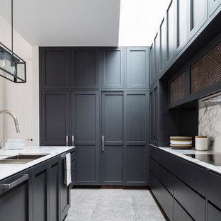 シドニーのコンテンポラリースタイルのおしゃれなアイランドキッチン (ダブルシンク、落し込みパネル扉のキャビネット、黒いキャビネット、パネルと同色の調理設備) の写真