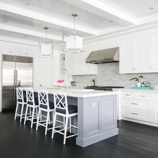 Large coastal open concept kitchen pictures - Example of a large beach style l-shaped dark wood floor open concept kitchen design in Orange County with white cabinets, marble countertops, gray backsplash, ceramic backsplash, stainless steel appliances, an island, shaker cabinets and a farmhouse sink