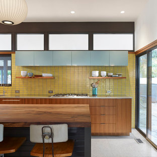 オースティンの中くらいのミッドセンチュリースタイルのおしゃれなキッチン (一体型シンク、フラットパネル扉のキャビネット、中間色木目調キャビネット、ステンレスカウンター、白いキッチンパネル、テラゾーの床) の写真