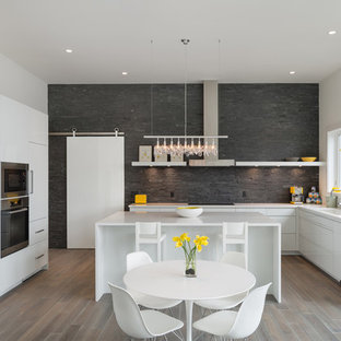 Design ideas for a contemporary l-shaped eat-in kitchen in Portland with flat-panel cabinets, white cabinets, panelled appliances, grey splashback and slate splashback.