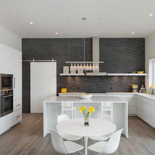 Создайте стильный интерьер: угловая кухня в современном стиле с обеденным столом, плоскими фасадами, белыми фасадами, техникой под мебельный фасад, серым фартуком и фартуком из сланца - последний тренд