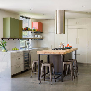 Small contemporary eat-in kitchen inspiration - Example of a small trendy l-shaped concrete floor eat-in kitchen design in Los Angeles with an undermount sink, flat-panel cabinets, light wood cabinets, marble countertops, white backsplash, stone slab backsplash, stainless steel appliances and an island