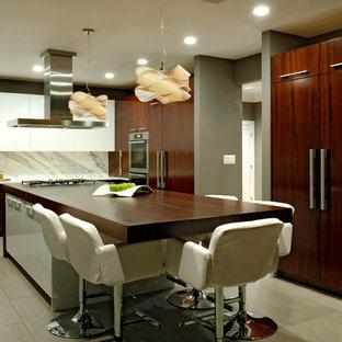 ボルチモアの大きいモダンスタイルのおしゃれなキッチン (アンダーカウンターシンク、フラットパネル扉のキャビネット、濃色木目調キャビネット、木材カウンター、白いキッチンパネル、パネルと同色の調理設備、大理石のキッチンパネル、クッションフロア、白い床) の写真