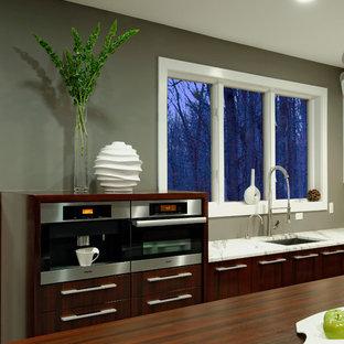 ボルチモアの大きいモダンスタイルのおしゃれなキッチン (アンダーカウンターシンク、フラットパネル扉のキャビネット、濃色木目調キャビネット、木材カウンター、白いキッチンパネル、パネルと同色の調理設備、大理石の床、クッションフロア、白い床) の写真