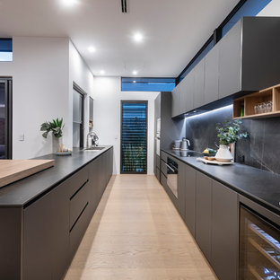 Inspiration for a contemporary galley kitchen in Perth with flat-panel cabinets, grey cabinets, grey splashback, black appliances, light hardwood floors, beige floor and grey benchtop.