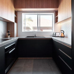 Inspiration for a contemporary u-shaped separate kitchen in Sydney with a drop-in sink, flat-panel cabinets, black cabinets, white splashback, black appliances, no island, grey floor and grey benchtop.