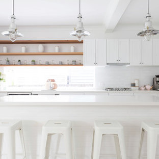 Inspiration for a mid-sized beach style single-wall kitchen in Sydney with an undermount sink, shaker cabinets, white cabinets, quartz benchtops, white splashback, subway tile splashback, stainless steel appliances, laminate floors, with island, beige floor and white benchtop.