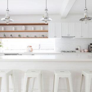 Idéer för att renovera ett mellanstort maritimt vit linjärt vitt kök, med en undermonterad diskho, skåp i shakerstil, vita skåp, bänkskiva i kvarts, vitt stänkskydd, stänkskydd i tunnelbanekakel, rostfria vitvaror, laminatgolv, en köksö och beiget golv