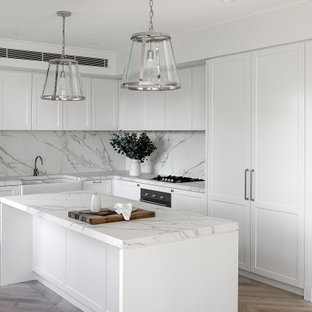 Photo of a mid-sized transitional l-shaped kitchen in Sydney with a farmhouse sink, shaker cabinets, white cabinets, white splashback, medium hardwood floors, with island, beige floor and white benchtop.