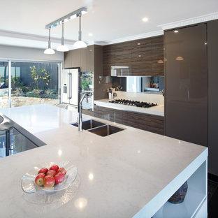 Idee per una grande cucina minimalista con lavello sottopiano, ante lisce, ante marroni, top in quarzo composito, paraspruzzi a effetto metallico, paraspruzzi con lastra di vetro, elettrodomestici in acciaio inossidabile, pavimento in marmo, isola, pavimento nero e top bianco