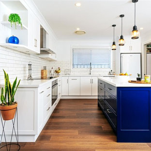 Photo of a mid-sized contemporary l-shaped kitchen in Other with white cabinets, solid surface benchtops, white splashback, ceramic splashback, white appliances, dark hardwood floors, with island, brown floor, white benchtop and recessed-panel cabinets.
