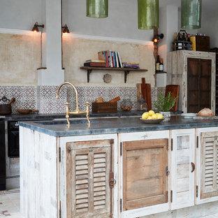 Удачное сочетание для дизайна помещения: линейная кухня среднего размера в средиземноморском стиле с врезной раковиной, фасадами с филенкой типа жалюзи, искусственно-состаренными фасадами, фартуком из цементной плитки, полом из цементной плитки, островом и разноцветным фартуком - самое интересное для вас