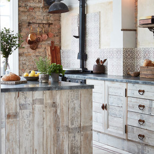 Inspiration for a country open plan kitchen in London with distressed cabinets, multi-coloured splashback, ceramic splashback, black appliances, ceramic floors, with island and multi-coloured floor.