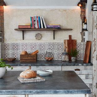 Immagine di una cucina mediterranea di medie dimensioni con lavello sottopiano, ante a persiana, ante con finitura invecchiata, paraspruzzi multicolore, paraspruzzi con piastrelle di cemento, pavimento con cementine e un'isola