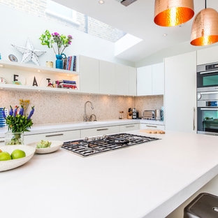 Photo of a large contemporary l-shaped kitchen/diner in London with a built-in sink, flat-panel cabinets, white cabinets, composite countertops, beige splashback, mosaic tiled splashback, stainless steel appliances, light hardwood flooring and an island.