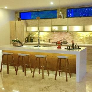 広いアジアンスタイルのおしゃれなキッチン (アンダーカウンターシンク、フラットパネル扉のキャビネット、淡色木目調キャビネット、人工大理石カウンター、マルチカラーのキッチンパネル、石タイルのキッチンパネル、シルバーの調理設備、大理石の床) の写真