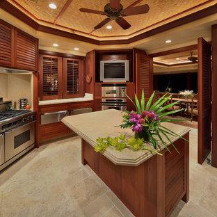 Große Küche mit Lamellenschränken, dunklen Holzschränken, Elektrogeräten mit Frontblende, Travertin, Kücheninsel und beigem Boden in Hawaii