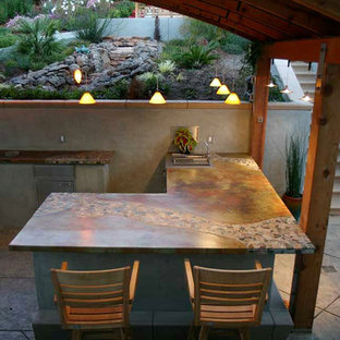 Large tropical eat-in kitchen ideas - Example of a large island style l-shaped concrete floor eat-in kitchen design in San Francisco with a double-bowl sink, concrete countertops, stainless steel appliances and a peninsula
