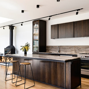 Design ideas for a mid-sized contemporary galley open plan kitchen in Other with a double-bowl sink, dark wood cabinets, marble benchtops, brown splashback, travertine splashback, stainless steel appliances, light hardwood floors, with island and brown benchtop.