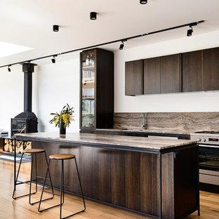 Diseño de cocina de galera, contemporánea, de tamaño medio, abierta, con fregadero de doble seno, puertas de armario de madera en tonos medios, encimera de mármol, salpicadero marrón, salpicadero de travertino, electrodomésticos de acero inoxidable, suelo de madera clara, una isla y encimeras marrones
