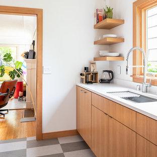 На фото: со средним бюджетом маленькие параллельные кухни в стиле модернизм с врезной раковиной, плоскими фасадами, светлыми деревянными фасадами, столешницей из кварцевого композита, белым фартуком, фартуком из керамической плитки, техникой из нержавеющей стали, полом из линолеума, островом, разноцветным полом и белой столешницей