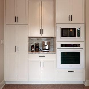 Ispirazione per una cucina american style di medie dimensioni con ante in stile shaker, ante bianche, elettrodomestici bianchi, pavimento in sughero, isola, paraspruzzi beige, lavello sottopiano, top in quarzite, paraspruzzi con piastrelle di vetro e pavimento marrone
