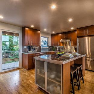 シアトルの中くらいのコンテンポラリースタイルのおしゃれなキッチン (アンダーカウンターシンク、フラットパネル扉のキャビネット、濃色木目調キャビネット、タイルカウンター、メタリックのキッチンパネル、メタルタイルのキッチンパネル、シルバーの調理設備、無垢フローリング、茶色い床) の写真