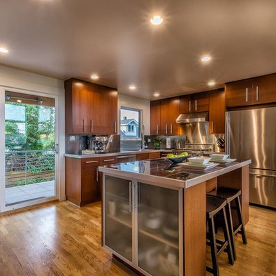Inspiration for a mid-sized contemporary l-shaped medium tone wood floor and brown floor open concept kitchen remodel in Seattle with an undermount sink, flat-panel cabinets, dark wood cabinets, tile countertops, metallic backsplash, metal backsplash, stainless steel appliances and an island