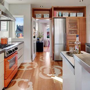 Идея дизайна: отдельная кухня в современном стиле с столешницей из цинка и цветной техникой