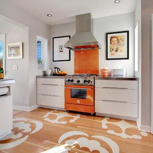 Geschlossene Moderne Küche mit flächenbündigen Schrankfronten, weißen Schränken, Küchenrückwand in Orange, Glasrückwand, bunten Elektrogeräten, Zink-Arbeitsplatte, gebeiztem Holzboden und buntem Boden in Seattle