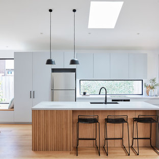 Photo of a mid-sized contemporary galley open plan kitchen in Melbourne with an undermount sink, grey cabinets, concrete benchtops, window splashback, light hardwood floors, with island, grey benchtop, flat-panel cabinets, stainless steel appliances and beige floor.