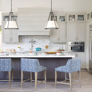 Coastal kitchen designs - Kitchen - coastal l-shaped light wood floor and beige floor kitchen idea in Miami with an undermount sink, shaker cabinets, gray cabinets, white backsplash, stainless steel appliances, an island and white countertops