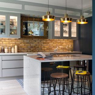 Einzeilige Industrial Wohnküche mit Glasfronten, grauen Schränken, Küchenrückwand in Beige, Rückwand aus Backstein und Kücheninsel in Dublin