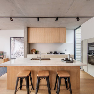 This is an example of a contemporary l-shaped kitchen in Sydney with an undermount sink, flat-panel cabinets, beige cabinets, black appliances, medium hardwood floors, with island, brown floor and white benchtop.