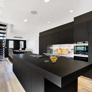Photo of a contemporary galley eat-in kitchen in Sydney with an integrated sink, flat-panel cabinets, black cabinets, metallic splashback, black appliances, light hardwood floors, with island and black benchtop.