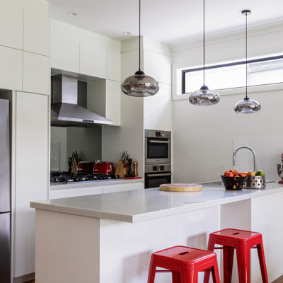 Inspiration for a contemporary galley medium tone wood floor and brown floor kitchen remodel in Sydney with flat-panel cabinets, white cabinets, stainless steel appliances, a peninsula and white countertops