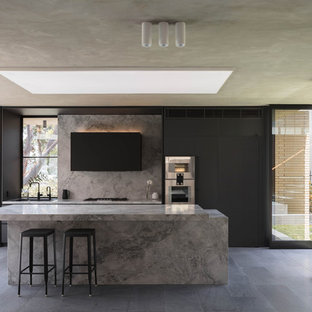 Bild på ett stort funkis grå grått parallellkök, med släta luckor, svarta skåp, rostfria vitvaror, en köksö, grått golv och marmorbänkskiva