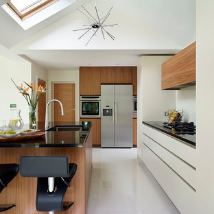This is an example of a medium sized contemporary kitchen in London with flat-panel cabinets, medium wood cabinets, granite worktops, an island, white floors, black worktops, a submerged sink and stainless steel appliances.