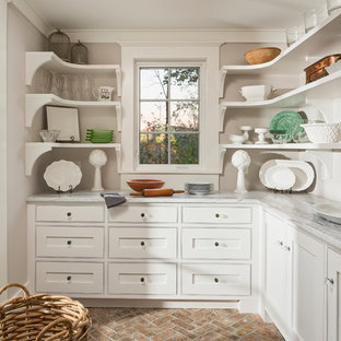 Photo of a rustic l-shaped kitchen pantry in Other with white cabinets, brick flooring and grey worktops.