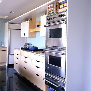 Moderne Küche mit flächenbündigen Schrankfronten, gelben Schränken, Marmor-Arbeitsplatte, Küchenrückwand in Blau, Küchengeräten aus Edelstahl, Betonboden und blauem Boden in Baltimore